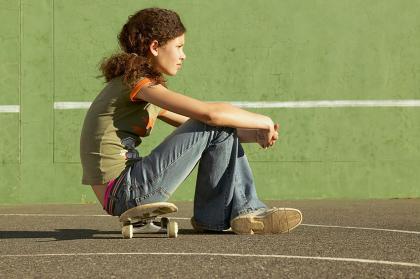 Teen girl sitting on skateboard