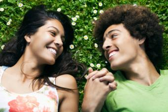 Teenage couple laying in grass