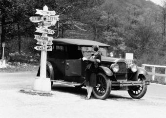 CIRCA 1920s: Woman leaning on car