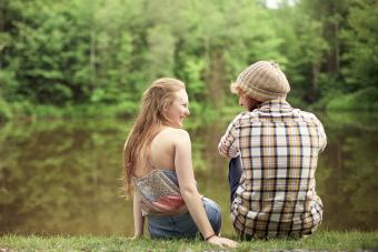 Rear view of couple sitting near lake