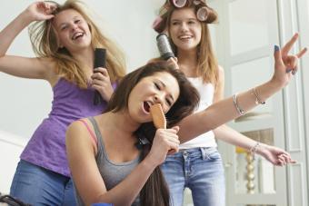 Teenage girls singing into hairbrushes