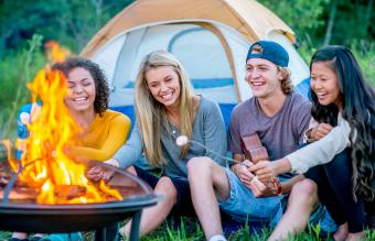 teenagers are sitting around a campfire