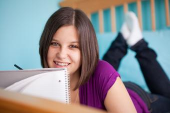 teen journaling on her bed