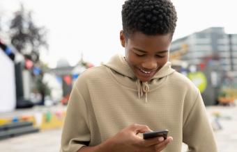 Smiling teenage boy texting