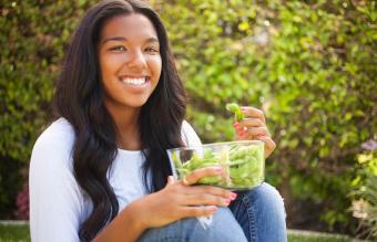 Teen girl eating edamame