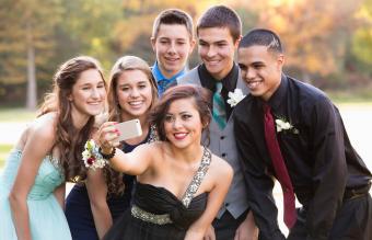 Teenagers taking selfie before prom