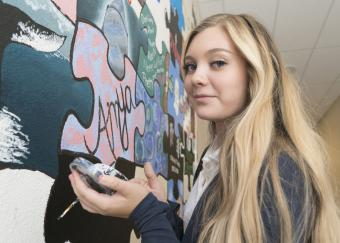 Teen girl painting a wall