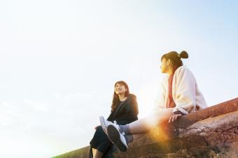 2 friends sitting on a wall