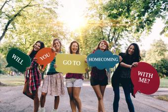 Girls holding Will You Go To Homecoming With Me? signs