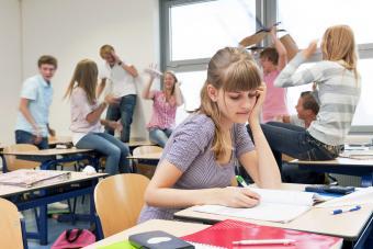 sad high school girl in chaotic classroom