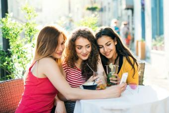 Teenager friends with smartphone sitting at the table in the outdoor cafe
