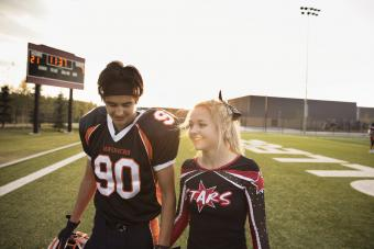 Teenage high school cheerleader and football player holding hands
