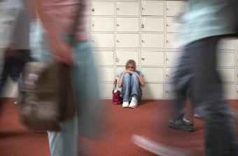 Teenage girl sitting by lockers in school hallway