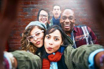 Group of happy friends take selfie outdoors