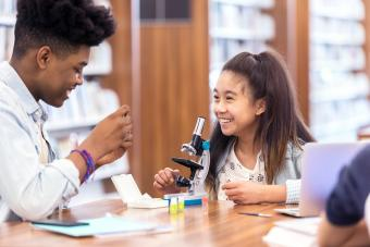 Smiling female student works on science assignment