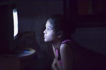 Teenager girl watching television in the dark