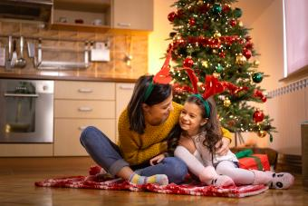 Babysitter playing with kid by the Christmas tree