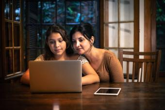 Mother helping her teenager doing homework at home at night