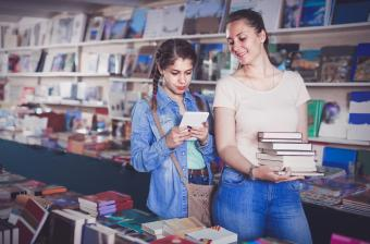 Teenager is buying books and searching information on tablet with her mom