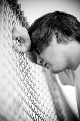 Image of a depressed teenager leaning on a fence