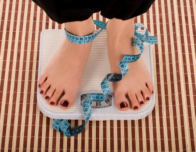 Teenager weighing herself on a scale with a measuring tape wrapped around her feet.