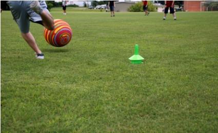 boy playing kickball