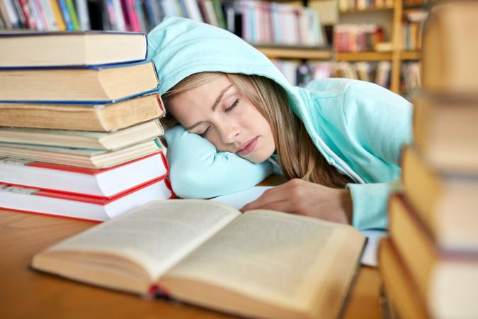 Student with books sleeping