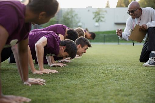 Physical education teacher encouraging students doing push-ups.
