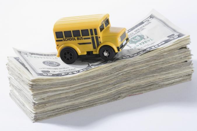 Toy bus sitting on stack of money