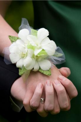 White orchid corsage on girl's wrist