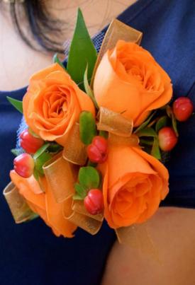 Orange flower corsage pinned to dress