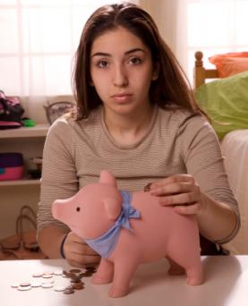 Teenager putting coin in piggy bank