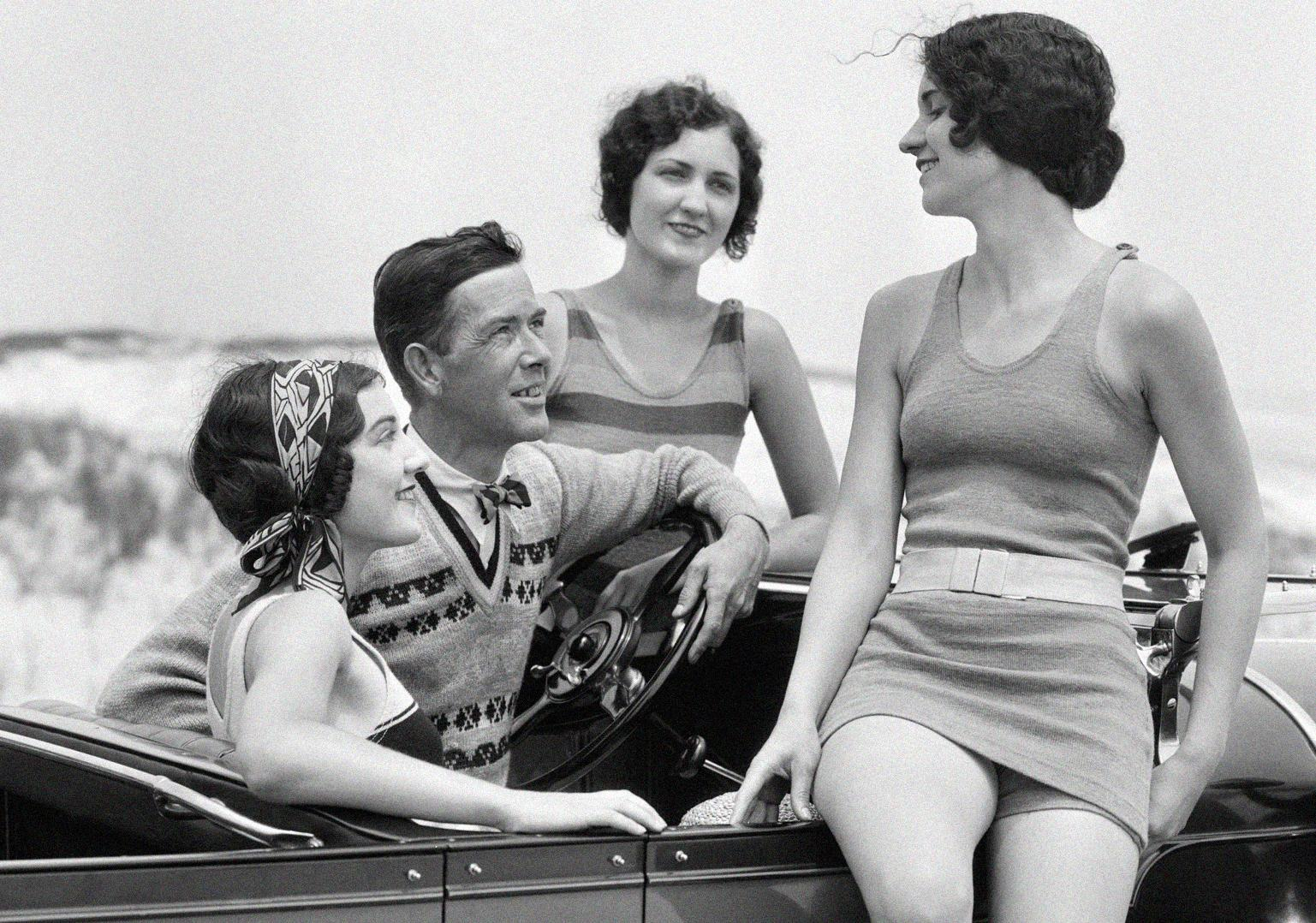 Man at steering wheel of convertible car, surrounded by three young women