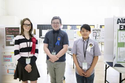 middle school students wearing prize ribbons at science fair