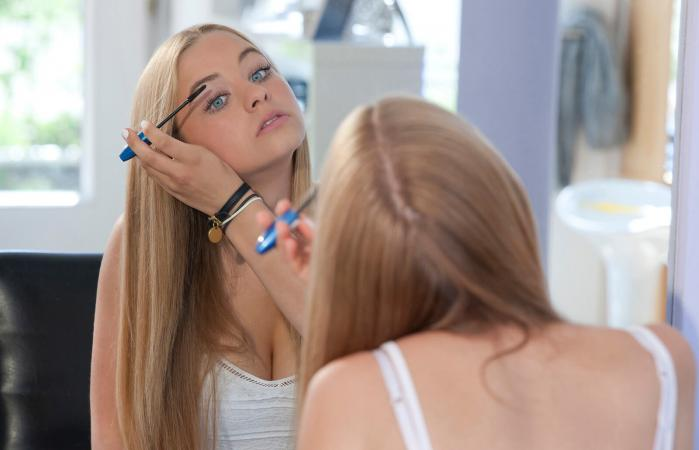 Teenage girl applying makeup
