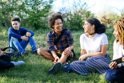 Teenagers sitting on grass laughing