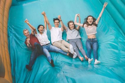 Teens Jumping Down Slide