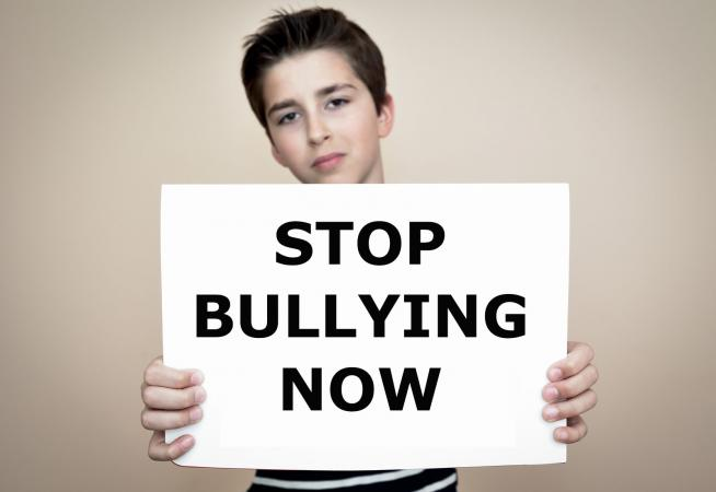 Boy holding stop bullying now poster