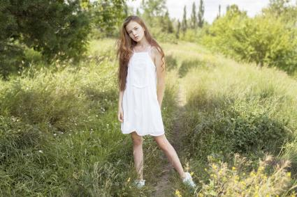 Girl standing in field of grass wearing a white summer dress