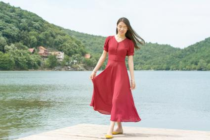 Girl standing in front of a lake wearing a long red dress