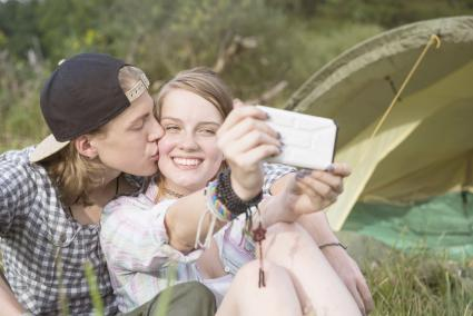 Young couple kissing and taking a selfie with smart phone