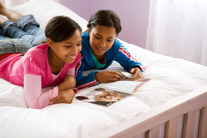 Tween girls reading a magazine