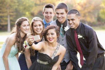 Teenagers taking selfie with cell phone before prom