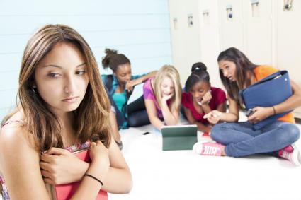 Teen girls with tablet cyber bullying a classmate