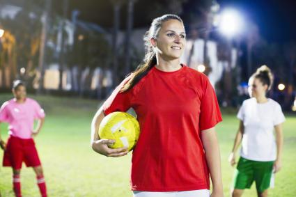 Smiling young female soccer player on field at night