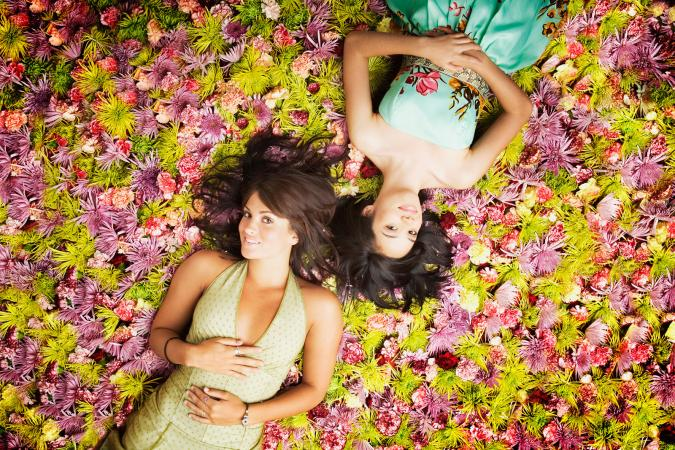 Women lying on grass with flowers