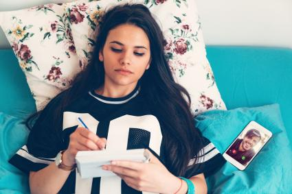Teenage girl writing in her journal in bed