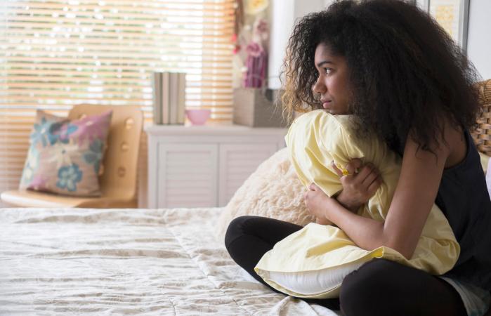 Depressed teenage girl in bed