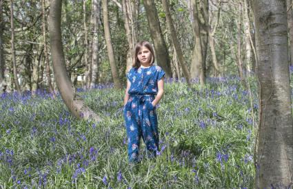 Child standing in the bluebell glen