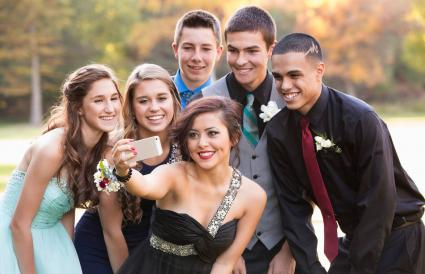 Teenagers taking selfie before prom